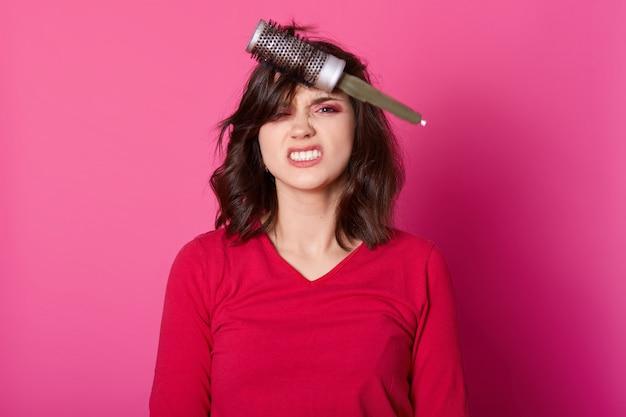 Mulher com cabelo problemático, senhora atraente se prepara para a festa, tenta soprar a escova de cabelo
