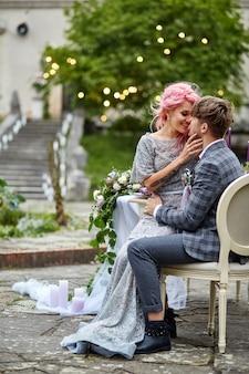 Mulher com cabelo rosa senta-se nos joelhos do homem na mesa de jantar em um quintal