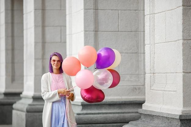 Mulher com cabelo roxo em copos-de-rosa em pé com um monte de airbaloons