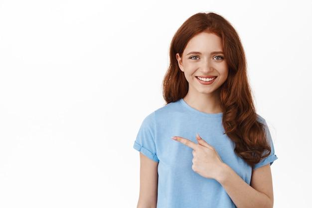Mulher com cabelo ruivo cacheado em uma camiseta, apontando o dedo para a esquerda, mostrando o espaço da cópia e sorrindo em pé no branco