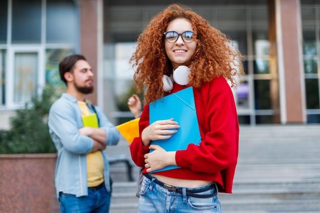 Mulher com cabelo ruivo cacheado na admissão na universidade