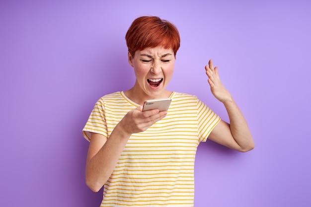 Mulher com cabelo ruivo curto grita para a tela do celular discutindo com alguém via smartphone online, irritada com alguma coisa