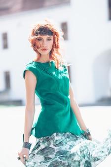 Mulher com cabelo ruivo e vestido verde