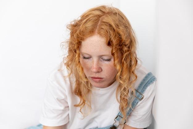 Mulher, com, cabelo ruivo, olhando baixo