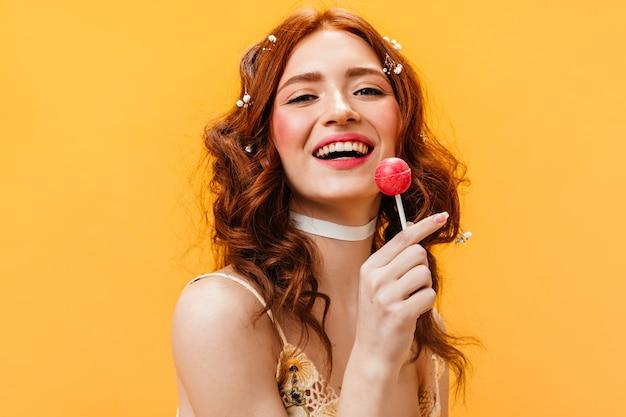 Mulher com cabelo ruivo ondulado ri e come pirulito. retrato de jovem em fundo laranja.