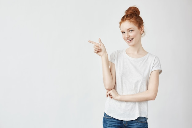 Mulher com cabelo sexy sorrindo apontando o dedo no lado.