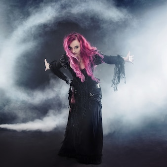 Mulher com cabelo vermelho em traje de bruxas, braços estendidos, vento forte