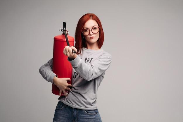 Mulher com cabelo vermelho, segurando um extintor de incêndio