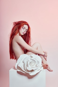 Mulher com cabelo vermelho sentado grande flor de papel