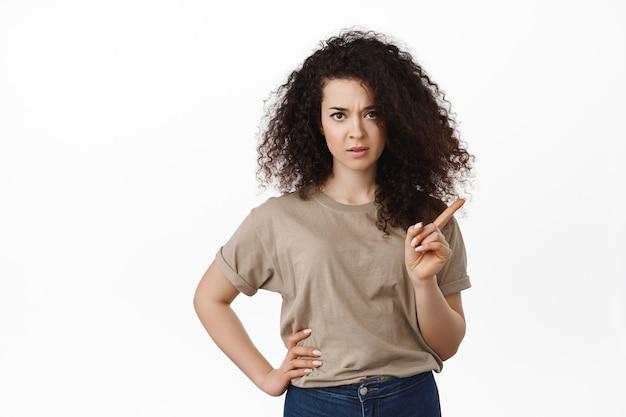 Mulher com cabelos cacheados balançando dedo, carrancuda e repreendendo alguém mal-comportado, desaprovar algo, dar aula, ficar de pé sobre o branco