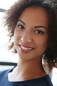 Mulher com cabelos cacheados e sorrindo