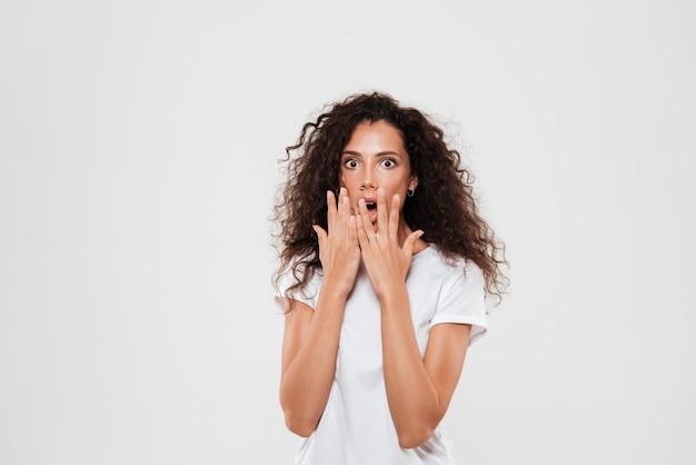 Mulher com cabelos cacheados em pé e cobrindo a boca com as mãos