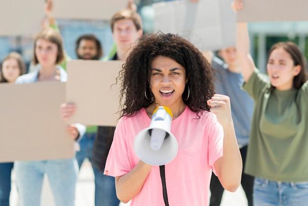 Mulher com cabelos cacheados, protestando com megafone