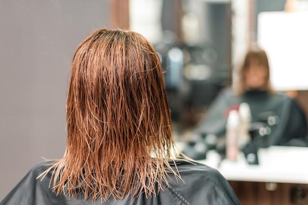 Mulher com cabelos castanhos compridos molhados.