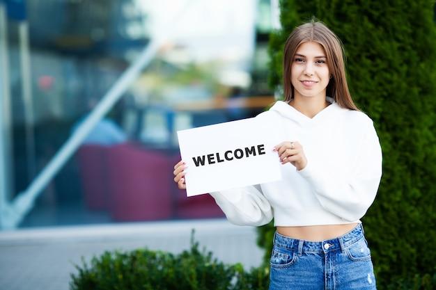 Mulher com cabelos compridos, segurando uma placa com a palavra de boas-vindas