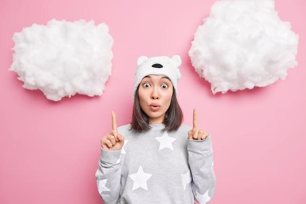 Mulher com cabelos escuros pontudos acima em nuvens brancas usa pijama confortável com poses de expressão facial rosa