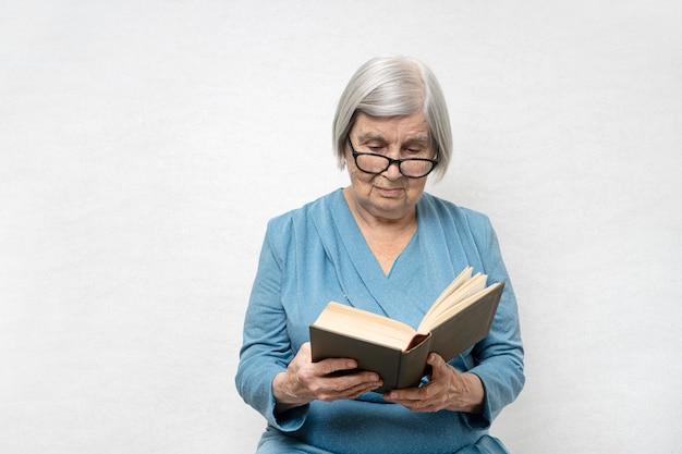 Mulher com cabelos grisalhos e pele enrugada lendo um livro
