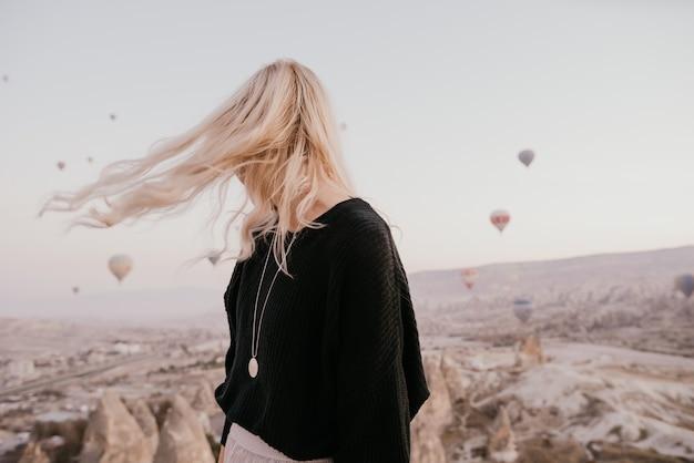 Mulher com cabelos loiros nas montanhas com balões na capadócia, turquia