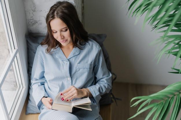 Mulher com cabelos longos escuros, focada no livro, lê algo emocionante, desfruta de uma atmosfera acolhedora em casa