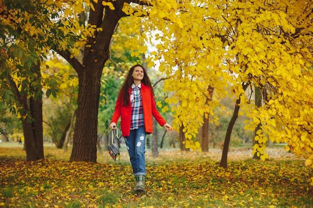 Mulher com cabelos longos ondulados, aproveitando o outono no parque.