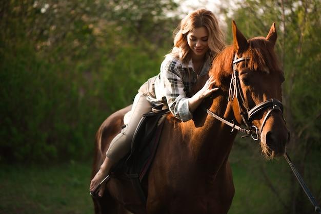 Mulher com cabelos longos, posando com um cavalo marrom em uma floresta em um campo ensolarado.