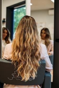 Mulher com cabelos longos, sentado em um cabeleireiro