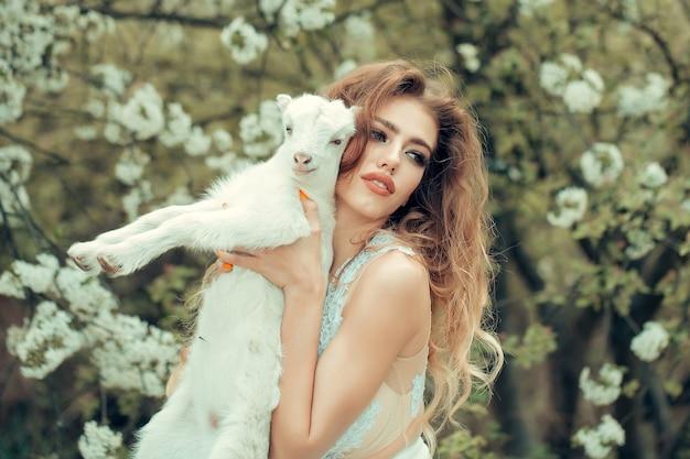 Mulher com cabra na floresta de flores ninfa em uma floresta de flores com cordeiro linda garota sensual jovem com cordeiro se parece com anjo de conto de fadas.