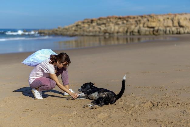 Mulher com cachorro catando lixo e plásticos limpando a praia