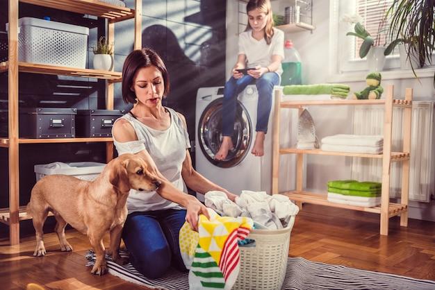 Mulher com cachorro classificando roupas no chão