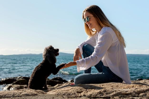Mulher com cachorro na beira-mar
