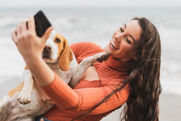 Mulher com cachorro tomando selfie