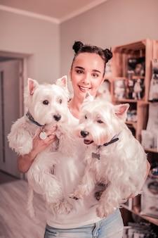 Mulher com cachorros. jovem bonita de olhos escuros com dois coques de cabelo segurando dois cachorros fofinhos