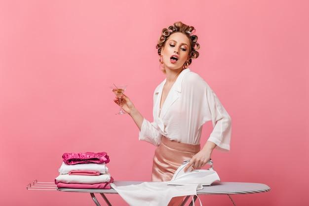 Mulher com cachos vestida com roupas elegantes, segurando uma taça de martini e passando roupa de cama