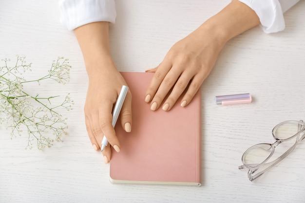 Mulher com caderno e caneta sobre fundo claro