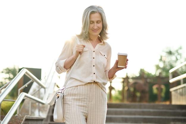 Mulher com café descendo escada