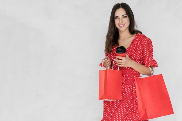 Mulher com café e sacolas de compras, olhando para a câmera