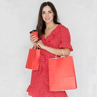 Mulher com café e sacolas de compras, sorrindo para a câmera