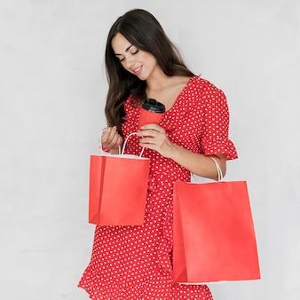 Mulher com café olhando nas sacolas de compras