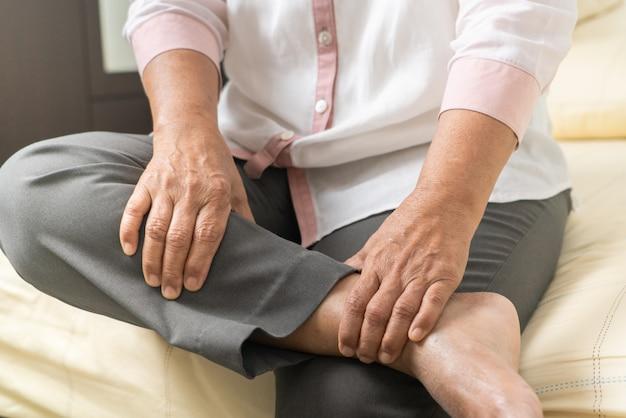 Mulher com cãibra nas pernas que sofre de cãibras em casa, problema de saúde do conceito sênior