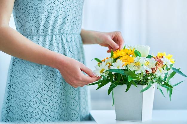 Mulher com caixa de chapéu decorativa de flores frescas coloridas e brilhantes no dia de primavera