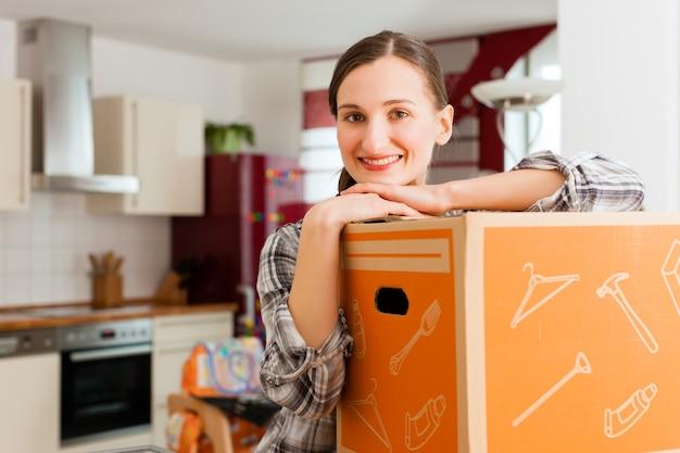 Mulher com caixa de mudança em casa