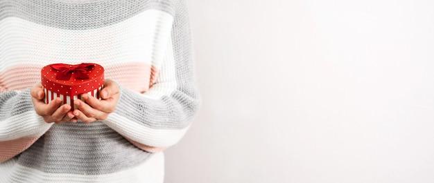 Mulher com caixa de presente de coração no dia dos namorados. foto panorâmica. copyspace.