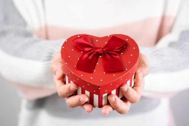 Mulher com caixa de presente de coração no dia dos namorados.