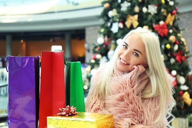 Mulher com caixa de presente e sacolas de compras na árvore de natal