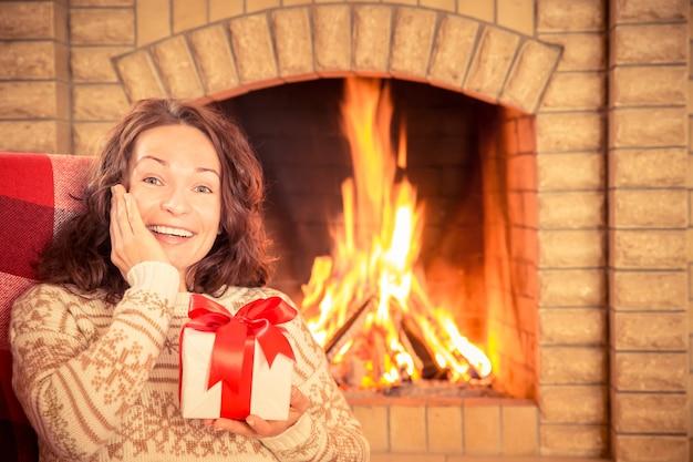 Mulher com caixa de presente perto da lareira. conceito de férias de inverno