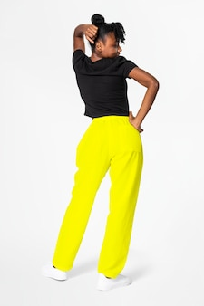 Mulher com calça de moletom amarelo neon e camiseta preta com roupas de rua, vista traseira
