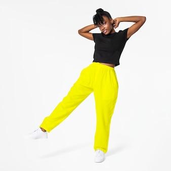Mulher com calça de moletom amarelo neon e roupa de rua preta