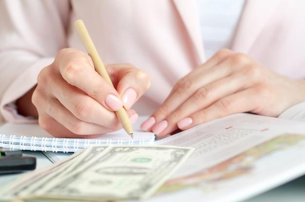 Mulher com calculadora contando e fazendo anotações no caderno.