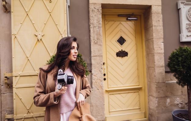 Mulher com câmera retro fica diante de portas amarelas