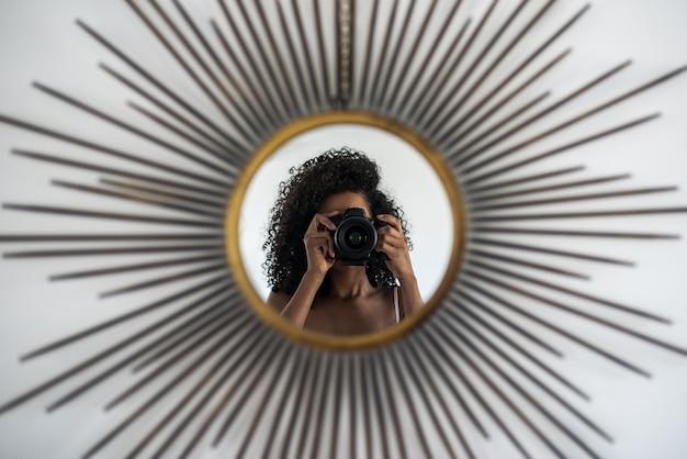 Mulher com câmera tirando foto de reflexão Foto Premium